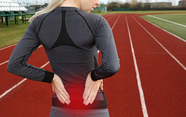 back pain. athletic fitness woman rubbing lower back. - low section stock photos and pictures