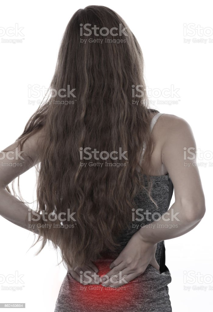 Back Pain. Athletic fitness woman rubbing the muscles of her lower back. Sport injury. stock photo
