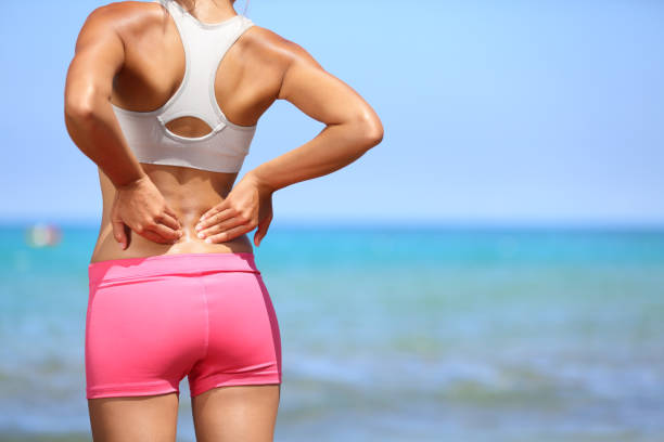 Back pain - Athletic woman rubbing her back stock photo