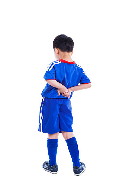 Back pain. Child rubbing muscles of his lower back, Isolated stock photo