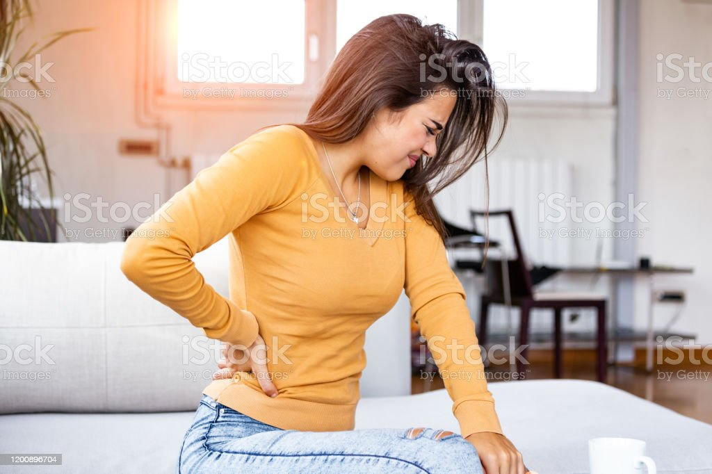 Back Pain Closeup Of Young Woman Having Spinal Or Kidney Pain Backache Girl Suffering From Painful Feeling Muscle Or Nerve Pain Holding Hands On Body Health Issue Concept Stock Photo Download