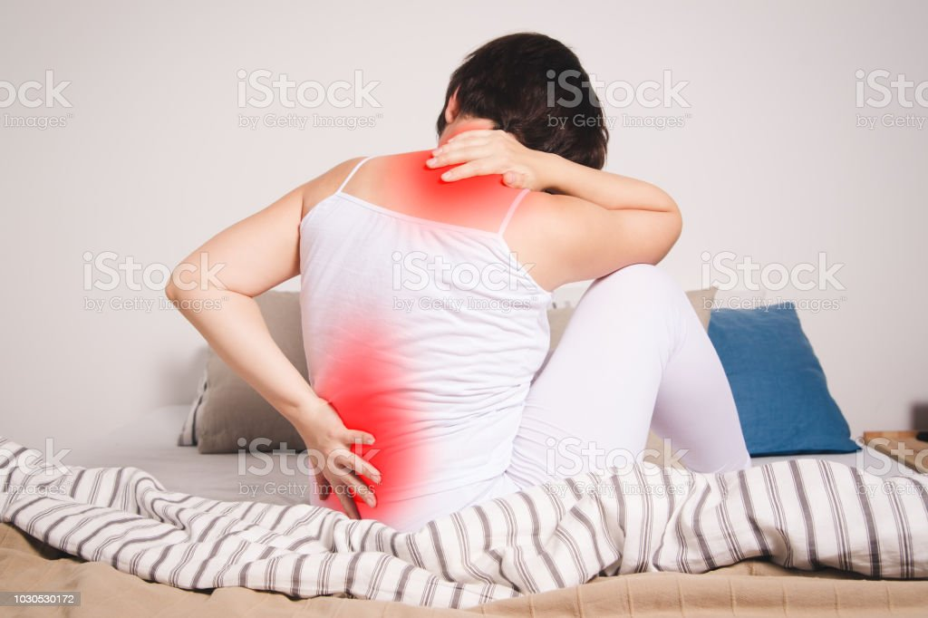 Back pain, kidney inflammation, woman suffering from backache at...