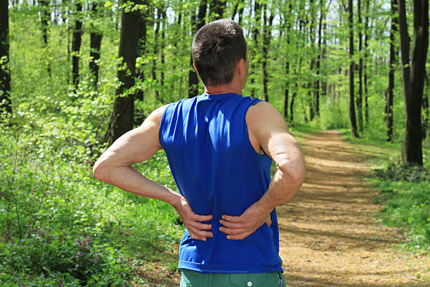 back pain. man runner lower back pain injury - low section stock photos and pictures