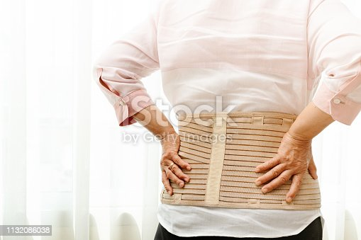 istock back pain, senior woman wearing back support belt on white background 1132086038