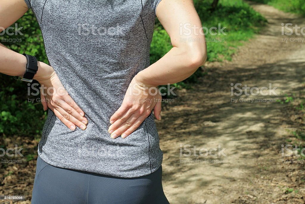 Back Pain. Woman rubbing the muscles of her lower back. stock photo