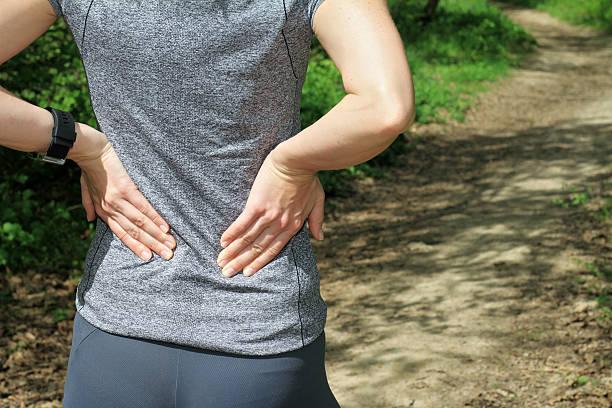 torna il dolore. donna di mettere i muscoli della sua parte inferiore della schiena. - ernia foto e immagini stock