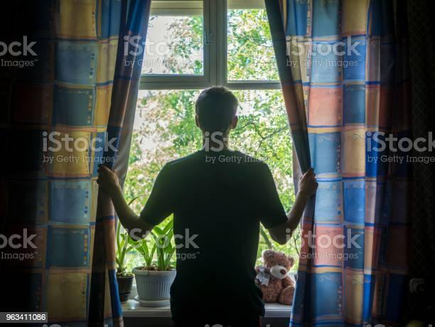 Tylny Portret Człowieka Otwierającego Zasłony Okna W Sypialni - zdjęcia stockowe i więcej obrazów Archiwalny