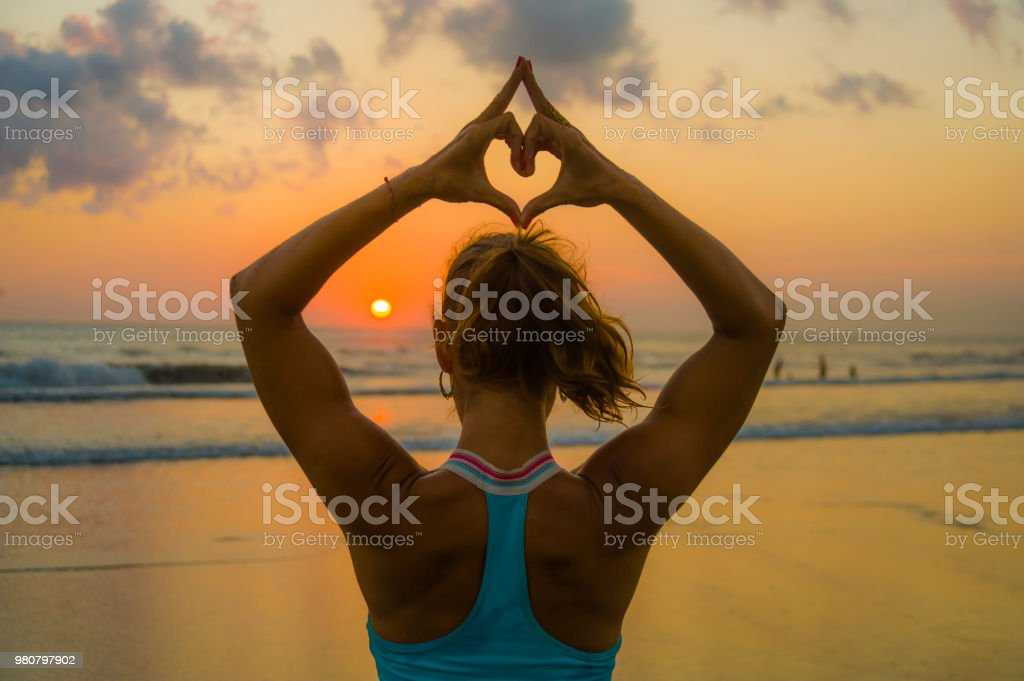 back portrait of young fit and healthy attractive woman doing love heart shape with hands and fingers against amazing beautiful sunset beach in yoga meditation and relaxation concept royalty-free stock photo