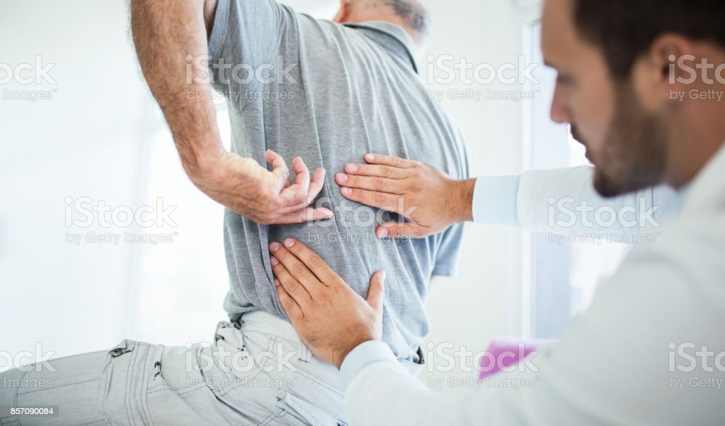 Back problems. Closeup rear low angle view of an early 60's senior gentleman having some back pain. He's at doctor's office having medical examination by a male doctor. The patient is pointing to his lumbar region. 50-59 Years Stock Photo