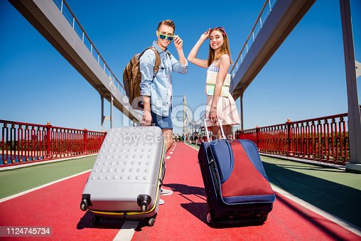 Back rear behind close up full length size body photo of excited glad cheerful handsome positive carefree careless cool nice beautiful boy lady hold suit case