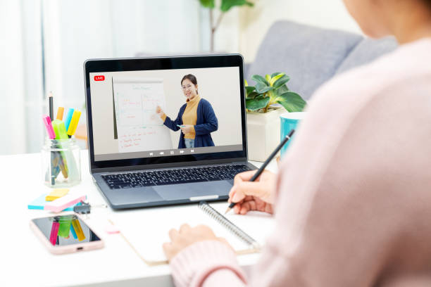 Back rear view of young asian girl sit on desk and learn at home living room in concept of romote learning, virtual online, self isolated quarantine lifestyle in asia. Teaching video call on computer. stock photo