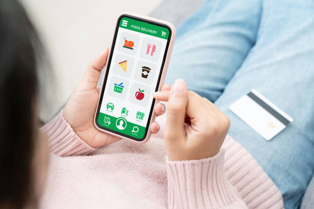 Back rear view of young asian teenage girl in concept next normal life from coronavirus impact using smart phone on hand and pay by credit card at home. Food delivery or grocery order service at home. stock photo