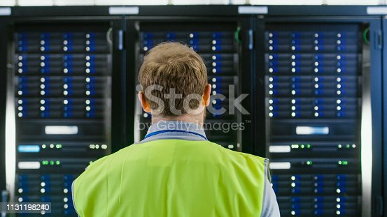 1131208605 istock photo Back Shot of an IT Administrator in High Visibility Vest Walking Towards a Server Rack in Data Center Room. 1131198240