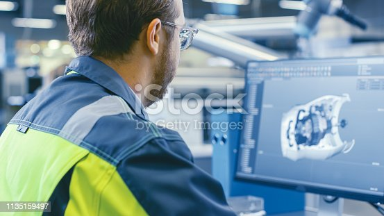 istock Back Shot of an Mechanical Engineer Working on Computers, Designing in 3D Model of the Engine using CAD Software. At the Factory. 1135159497