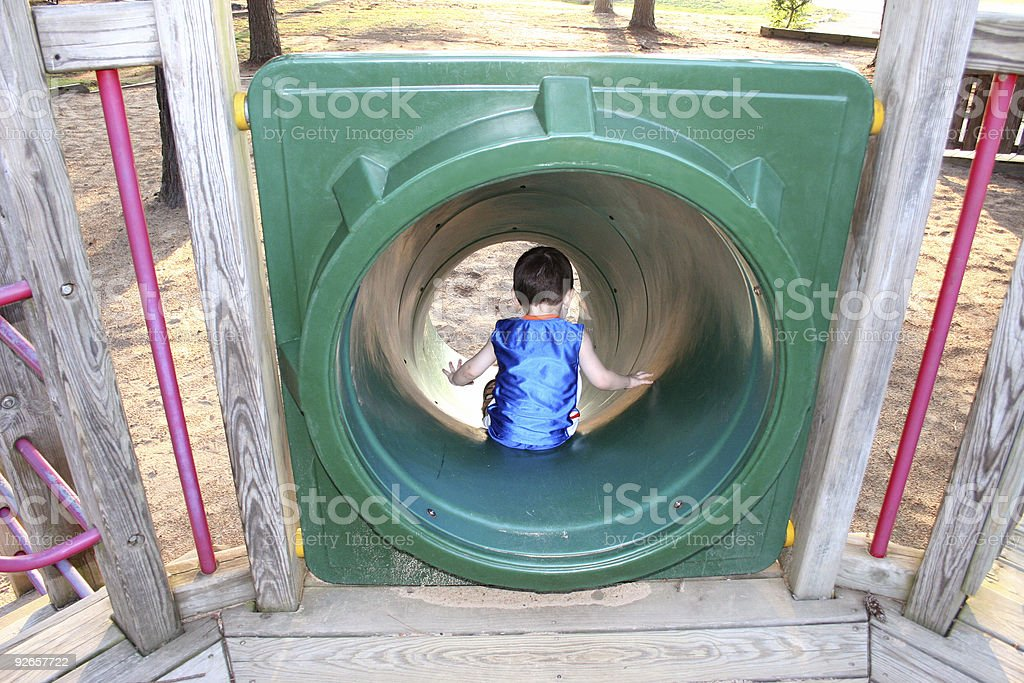 Back Side of Boy Going Down Park Slide royalty-free stock photo