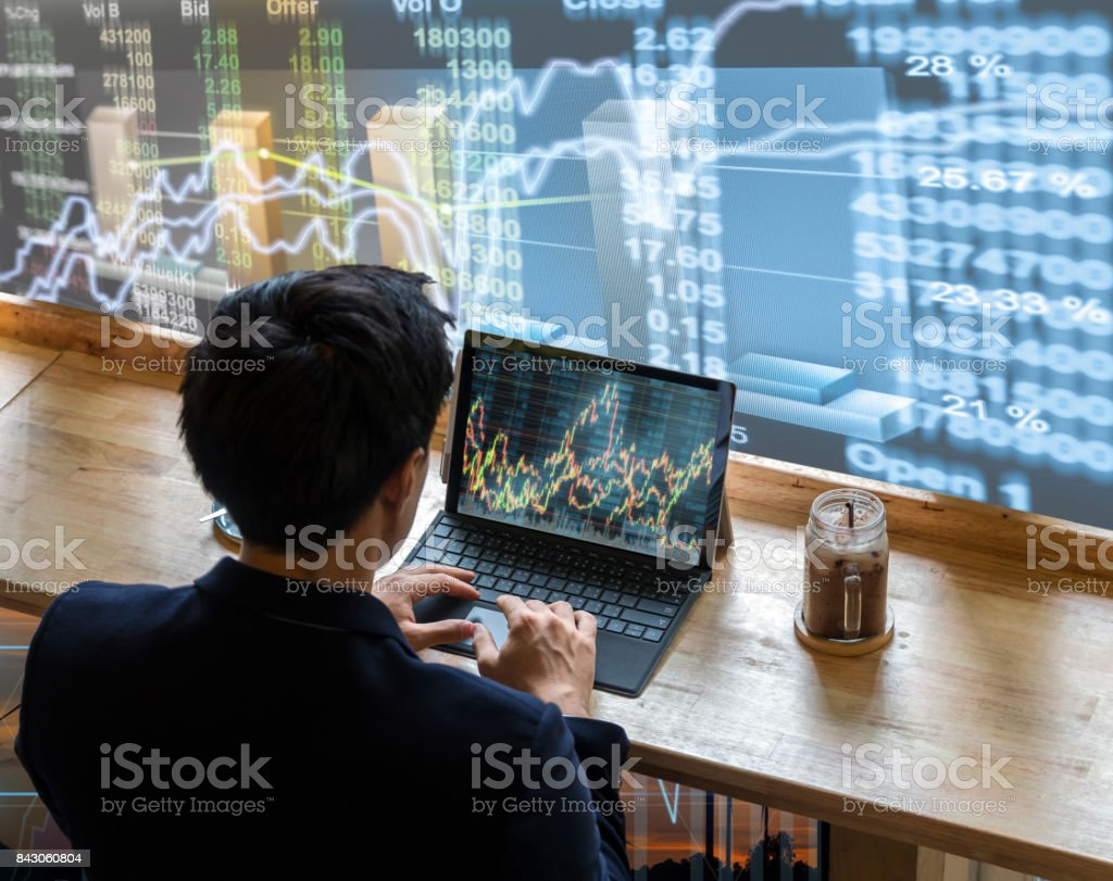 Back side of Businessman sitting and using computer laptop showing trading graph beside the windows glass over the stock market chart background, Business financial and trading concept stock photo