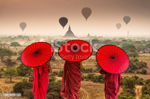 1035635902 istock photo Back side of three Buddhist novice are walking over the Ancient Temples in Bagan with hot air on the sky at sunrise time, Myanmar 1082939150