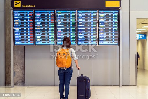 842907838 istock photo Back side of traveler with luggage standing over the flight board for check-in at the flight information screen in modern an airport, travel and transportation with technology concept. 1135326160