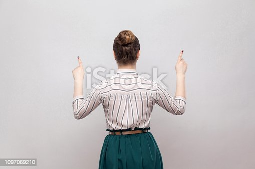 istock Back side portrait of beautiful young woman in striped shirt and green skirt and collected ban hairstyle, standing and pointing at up side copyspace. 1097069210