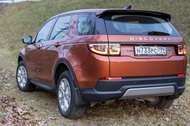 Back side View of all new premium england suv. Land rover Discovery sport parked in the forest. Orange all wheel drive car standed on the ground. stock photo