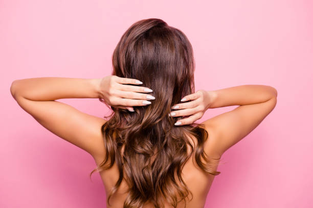 Back side view of shirtless, naked, attractive, young girl straighten her hair, having trendy, modern manicure, preparing for date, isolated on pink background Back side view of shirtless, naked, attractive, young girl straighten her hair, having trendy, modern manicure, preparing for date, isolated on pink background hair stock pictures, royalty-free photos & images