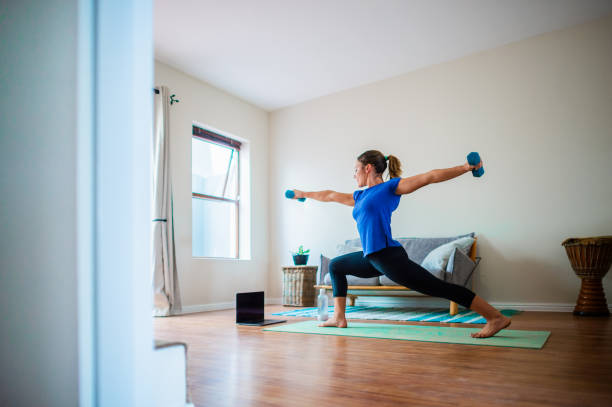 Back side view Young girl doing online exercise session at home with dumbbells arms stretched out stock photo