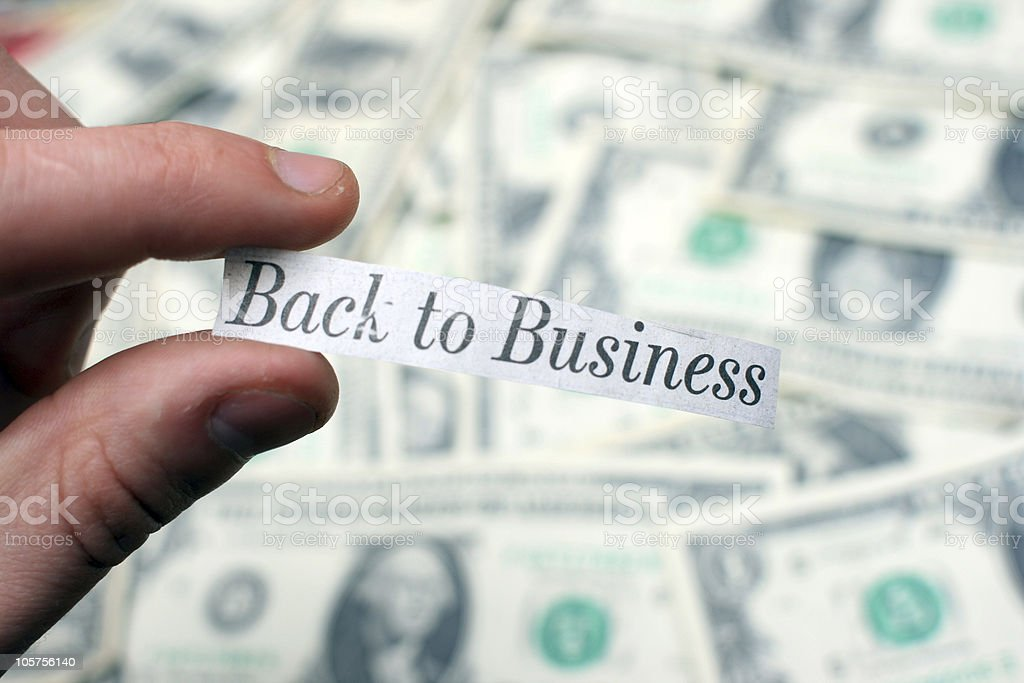 'Back to Business' - Positive Newspaper Headline Against Dollar Bills stock photo