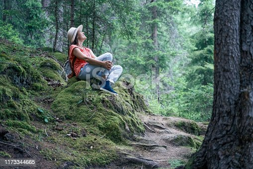 A Cheerful Adult tourist having fun in the Nature. Casual Clothing, Woman in a pine woodland. Weekend Activities.
