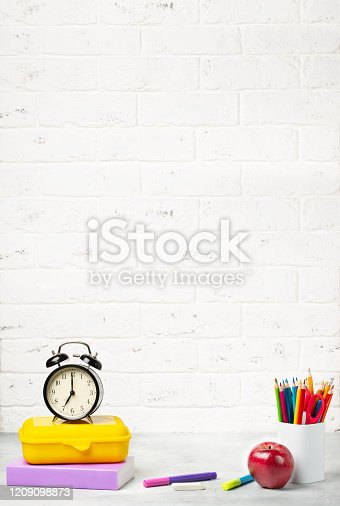 Back to school 1 September. Alarm clock, books, notebooks, pencils and lunch box on the table.