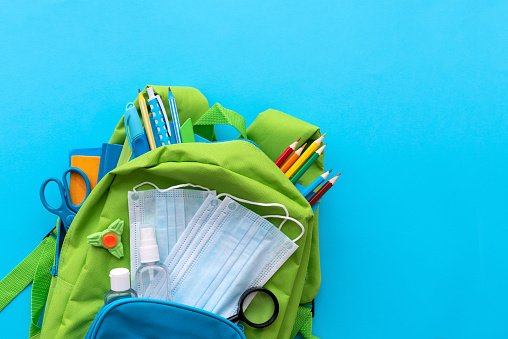 Back to school after quarantine concept. Backpack with school supplies and set of sanitizers and medical protective masks on