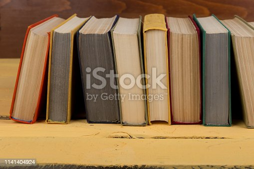 istock Back to school and education concept - colorful hardback books on yellow wooden table on brown wooden background 1141404924