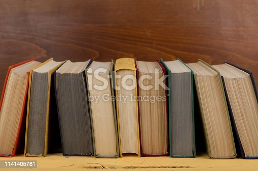 istock Back to school and education concept - colorful hardback books on yellow wooden table on brown wooden background 1141405781