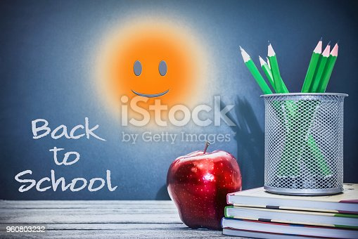istock Back to School and Education concept. Sunny smile in classroom with apple, books and pencils on chalkboard background 960803232