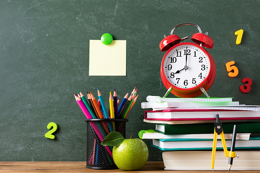 1045293630 istock photo Back to school and education concept with alarm clock, green apple and stationery supplies against blackboard. Starting new school year background. 1257951553