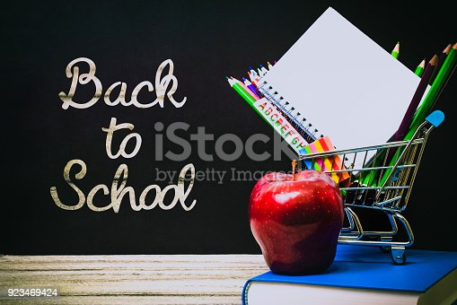 istock Back to School and Education shopping concept. classroom with apple, books and pencils on chalkboard background 923469424