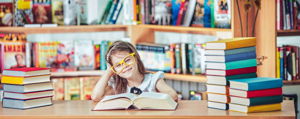 Back to school and happy time! Cute industrious child is sitting at a desk indoors. stock photo