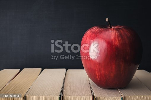 881192038 istock photo Back to School - apple and on stacked books in front of a blackboard at 1181594241
