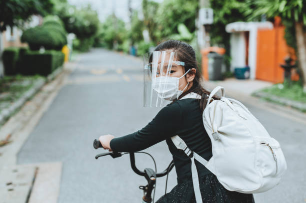 Back to school. asian child girl wearing face mask with backpack biking a bicycle and going to school .Covid-19 coronavirus pandemic.New normal lifestyle.Education concept. Back to school. asian child girl wearing face mask with backpack biking a bicycle and going to school .Covid-19 coronavirus pandemic.New normal lifestyle.Education concept. bycicle stock pictures, royalty-free photos & images