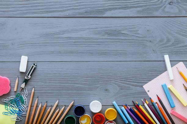 Zurück zum Hintergrund Schulkonzept mit Freiexemplar Platz für Text, moderne Zubehör Schreibwaren, Farbstiften, Lacke, Papier auf dunklen grauen Holztisch, moderne Grundschule, Ansicht von oben – Foto