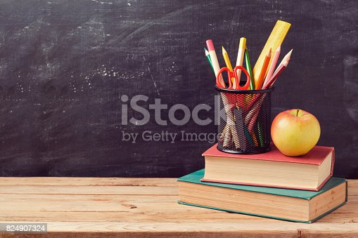 istock Back to school background with books, pencils and apple over chalkboard 824907324