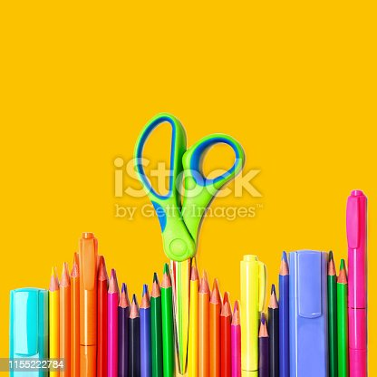 istock Back to school background with colorful pencils, scissors, markers on yellow backdrop, isolated. 1155222784