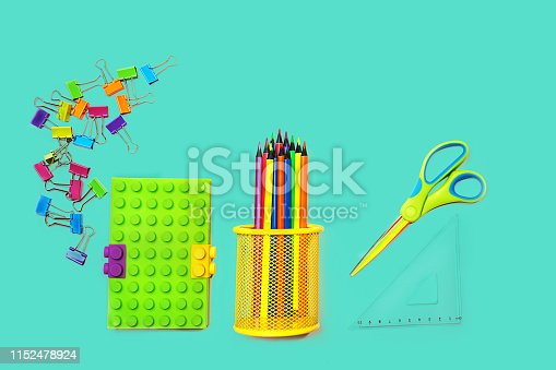 istock Back to school background with notepad, colorful paper clips, pencils, square ruler, scissors on pastel blue green backdrop. 1152478924