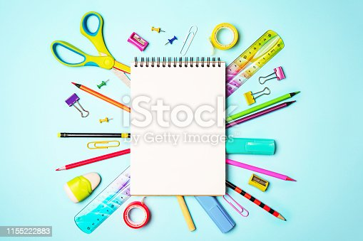istock Back to school background with notepad, colorful pencils, square ruler, scissors, clips on pastel blue backdrop. 1155222883