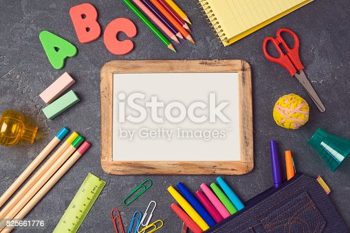 istock Back to school background with poster mock up and school supplies.View from above. Flat lay 825661776