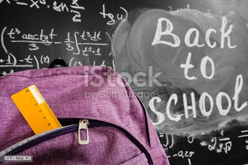 istock Back to school background with purple school bag with yellow ruler and the title