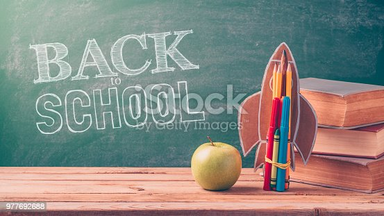 Back to school background with rocket made from pencils, apple and old books over chalkboard