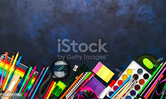 istock Back to school background with space for text, notebooks, pens, pencils, other stationery on blue chalk board desk, education concept, flat lay, top view 1163812984