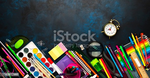 istock Back to school background with space for text, notebooks, pens, pencils, other stationery on blue chalk board desk, education concept, flat lay, top view 1163812985