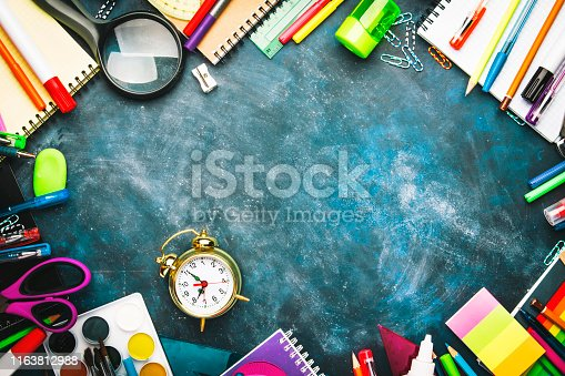 istock Back to school background with space for text, notebooks, pens, pencils, other stationery on blue chalk board desk, education concept, flat lay, top view 1163812988