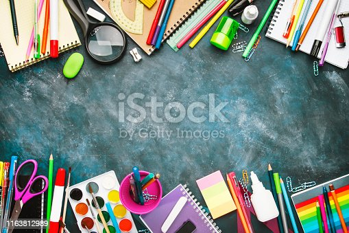 istock Back to school background with space for text, notebooks, pens, pencils, other stationery on blue chalk board desk, education concept, flat lay, top view 1163812989